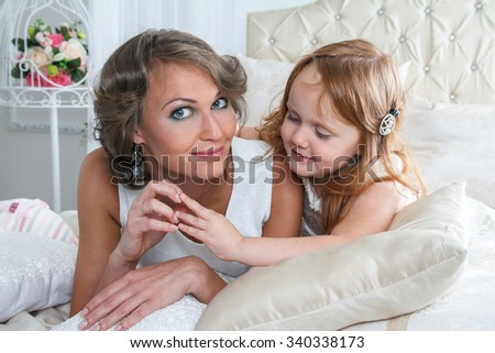 image of young attractive mother and her pretty red haired daughter lying on bed together smiling - stock photo