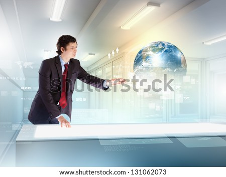 Image of young businessman clicking icon on high-tech picture of globe.Elements of this image are furnished by NASA - stock photo