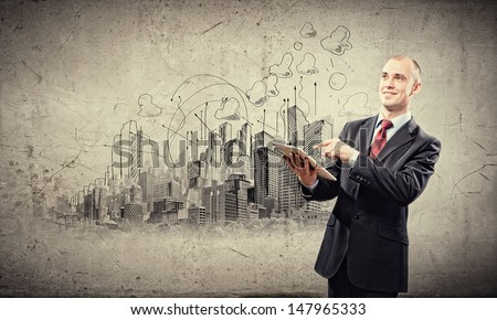 Image of young businessman holding ipad against sketch background - stock photo