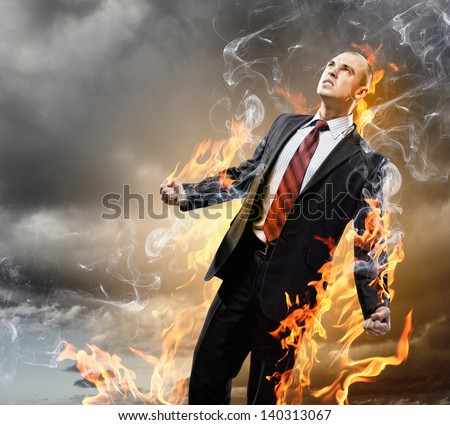 Image of young businessman in anger burning in fire - stock photo