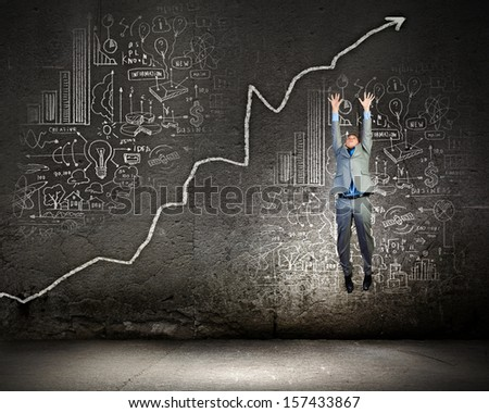 Image of young businessman jumping above graph - stock photo