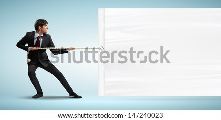 Image of young businessman pulling blank banner. Place for text - stock photo