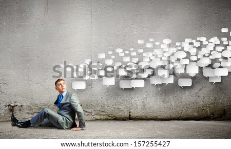 Image of young businessman sitting on floor - stock photo