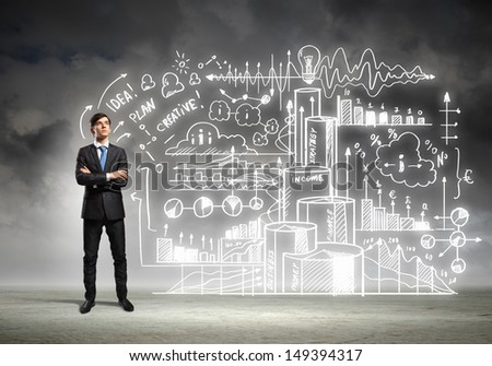 Image of young businessman standing against business sketch - stock photo
