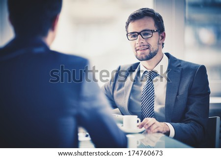 Image of young businessman with cup of coffee communicating with his colleague - stock photo