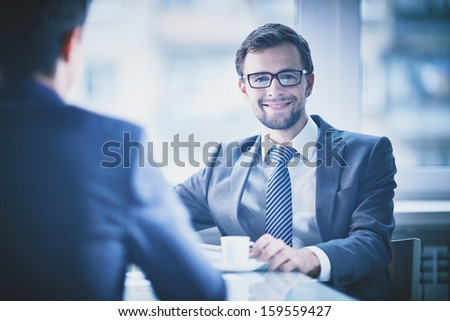 Image of young businessman with cup of coffee looking at camera - stock photo