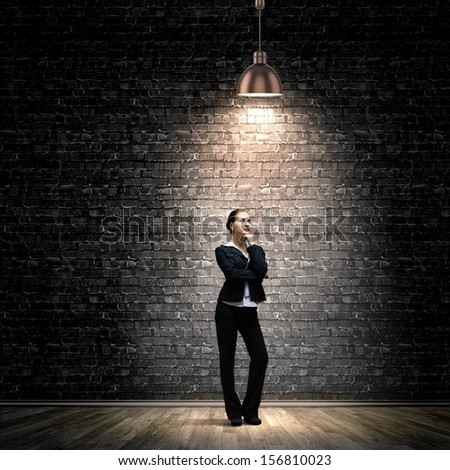 Image of young businesswoman standing under spot of light - stock photo