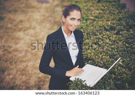Image of young businesswoman with laptop looking at camera while networking in park - stock photo