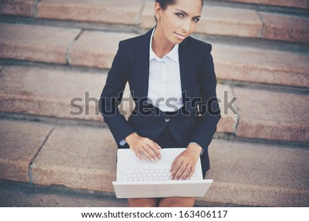 Image of young businesswoman with laptop networking on steps of building - stock photo