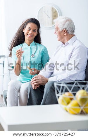 Image of young carer keeping senior patient company - stock photo