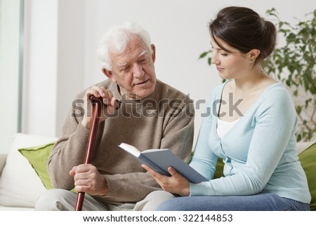 Image of young carer reading book to senior man  - stock photo