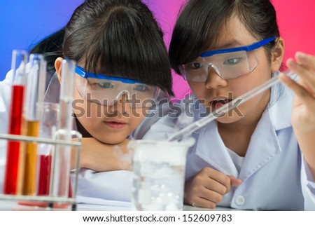 Image of young children making a chemical experiment in the laboratory - stock photo