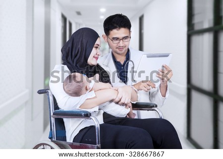 Image of young doctor showing digital tablet on the disabled woman sitting on the wheelchair with her baby - stock photo