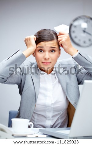 Image of young employer touching her head in confusion at workplace - stock photo