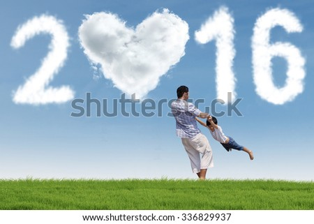 Image of young father playing on the meadow with his son under cloud shaped numbers 2016 - stock photo