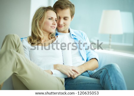 Image of young female and her husband resting on sofa in new flat - stock photo