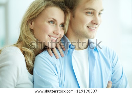 Image of young female embracing her husband and both looking forwards in new flat - stock photo