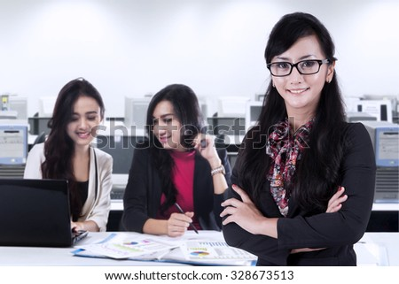 Image of young female manager standing in the office with two partners working on the back - stock photo