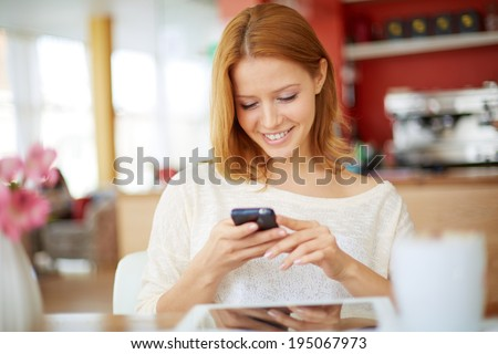 Image of young female reading sms on the phone in cafe - stock photo