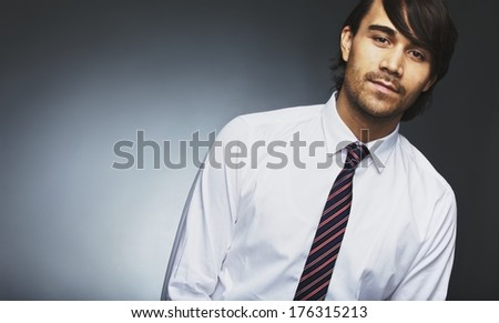 Image of young male model in formal wear looking at camera. Mixed race businessman posing against grey background with lots of copyspace. - stock photo