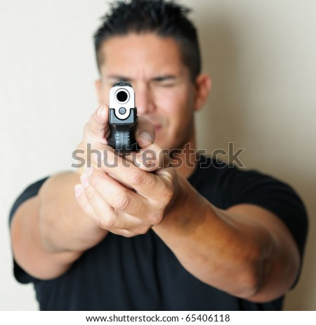 Image of young male pointing gun.  Focus on barrel of gun. - stock photo