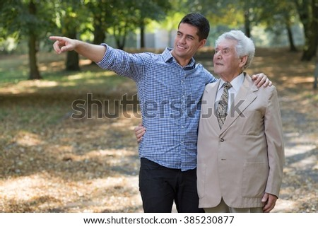 Image of young man showing something grandfather - stock photo