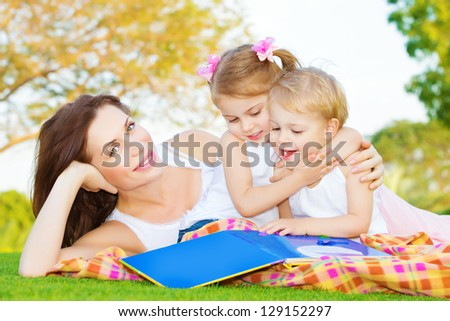 Image of young mother with two cute little kids spending time outside in spring time, beautiful woman lying down on green field near her children, sister hugging brother and read book, happy family - stock photo