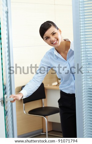 Image of young pretty secretary opening office door and looking at camera - stock photo