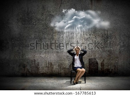 Image of young troubled businesswoman standing under rain - stock photo