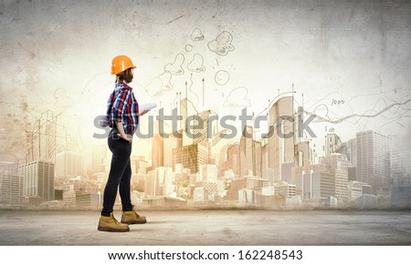 Image of young woman engineer with project against sketch background - stock photo