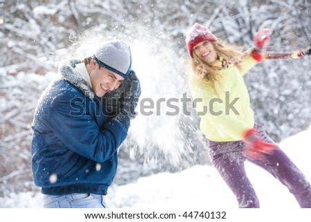 Image of young woman flinging the snowball into her boyfriend - stock photo