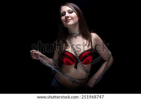 Image of young woman in bra with chain on black background - stock photo