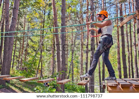 Image of young woman on course in mountain helmet and safety equipment. - stock photo
