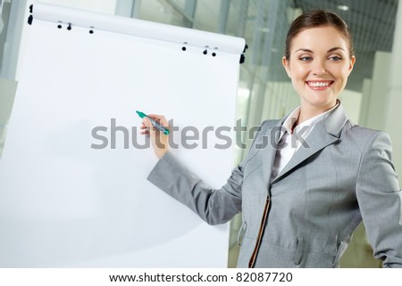 Image of young woman pointing at whiteboard at meeting - stock photo