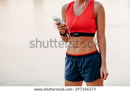 Image of young woman taking a break form workout using mobile phone outdoors. - stock photo