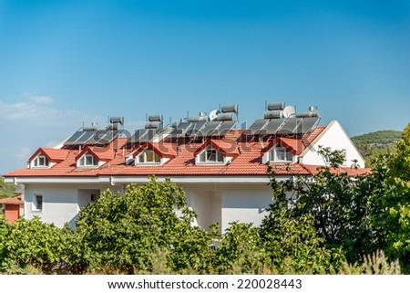 Image showing solar panels and water storage tanks on the top of houses in hisaronu, Turkey with blue sky and room for copy space - stock photo