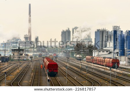 Image showing trains against an industrial background with factories pumping coal fumes into the atmosphere - stock photo