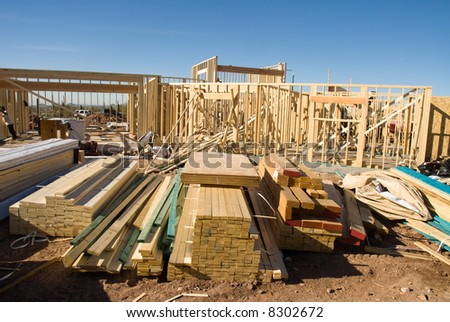 Image shows a home under construction at the framing phase.  Ideal for home construction advertising and other home construction promotional inferences. - stock photo
