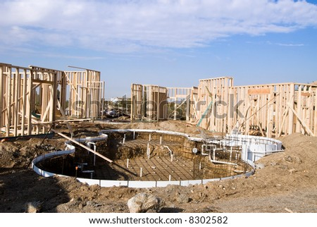 Image shows a home under construction at the framing phase with pool construction.  Ideal for roofing advertising and other home construction promotional inferences. - stock photo