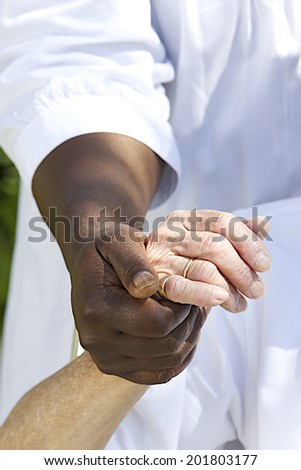 Image Symbol of comfort and support from care giver to elderly woman outdoor holding her hand - stock photo