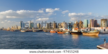 Image with a lot of ships in port. In the background the skyscrapers of Dubai. - stock photo