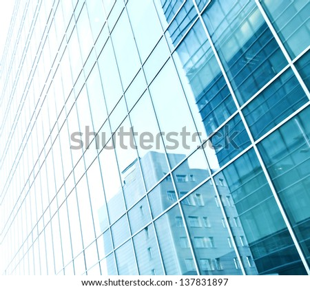 Image with reverberation of underside panoramic and perspective view to steel blue glass high rise building skyscrapers Business concept of successful industrial architecture with curve and bent lines - stock photo