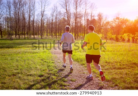 Image with two man jogging in a park - stock photo
