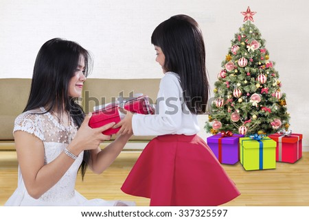 Images of a lovely girl giving a christmas gift on her mother at home with a christmas tree background - stock photo