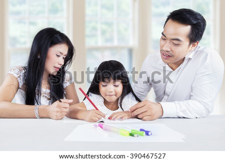 Images of smart little girl studying and write on the book with her parents at home - stock photo