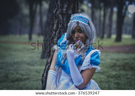 imagination, alice in wonderland, girl in a forest with smoke colore and playing cards - stock photo