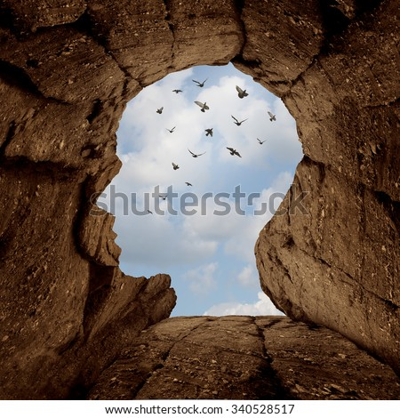 Imagination and discovery concept as a rocky cliff with an opening on top shaped as a human head as a new life metaphor and success motivation symbol with a group of birds flying high in the sky. - stock photo
