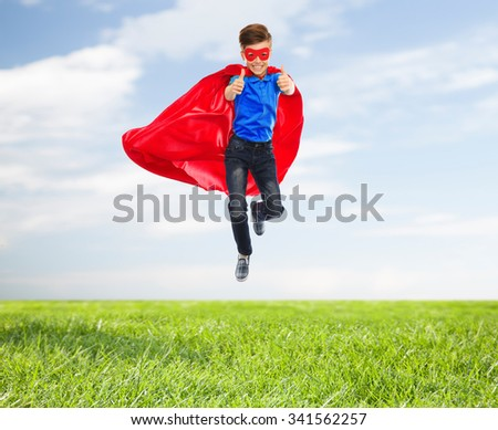imagination, gesture, childhood, movement and people concept - boy in red super hero cape and mask flying in air and showing thumbs up over blue sky and grass background - stock photo