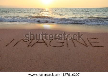 Imagine written in the sand on a sunset beach. - stock photo