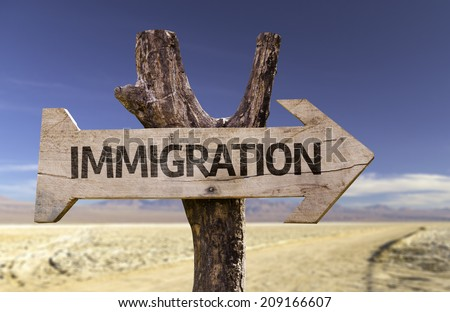 Immigration wooden sign with a desert background - stock photo